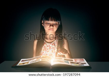 Little asian girl reading the book - stock photo