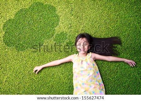 Little asian girl resting on green grass - stock photo