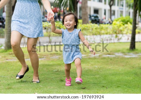 Little Asian girl running with her mother in the park - stock photo