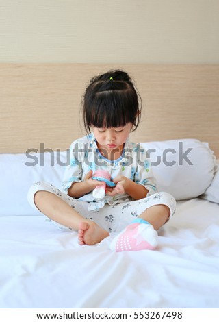 little asian girl trying to put a socks on the bed.