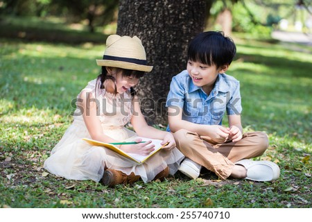 Little asian girl use pencil writting on notebook for writing book with smiling face in the park and her brother looking to her - stock photo