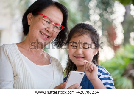 Little Asian girl using mobile phone with her grandmother - stock photo