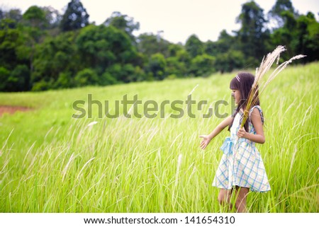 Little asian girl walking outdoors in a meadow - stock photo