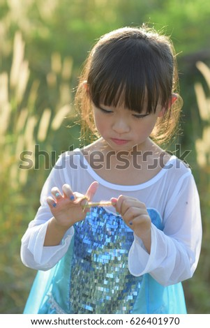 Little asian girl wearing a princess dress in action in grass fields.