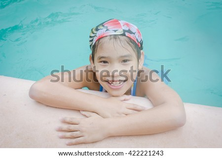 little Asian girl wearing swimming suit playing in swimming pool