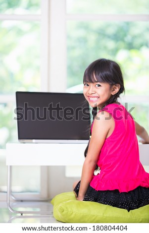 Little asian girl with a laptop computer at home - stock photo