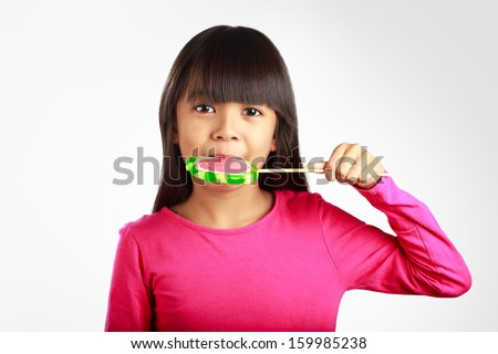 Little asian girl with a lollipop, Isolated over grey with clipping path - stock photo
