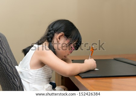Little Asian girl with glasses writing at the table