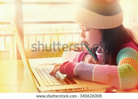little asian girl working on laptop - stock photo