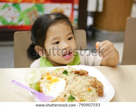 Little Asian kid, a girl, catching a piece of carrot while having fried rice by herself