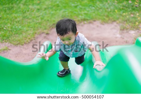 Little Asian kid climbing up the slide at the playground under the sunlight in summer, Kids play on school yard. Happy kid in kindergarten or preschool. shallow DOF