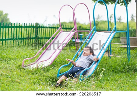 Little Asian kid playing slide at the playground under the sunlight in summer, Kids play on school yard. Happy kid in kindergarten or preschool. shallow DOF