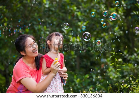Little asian lovely girl and her mother blowing soap bubbles on blurred nature background. Outdoors. Loving and happy family. - stock photo