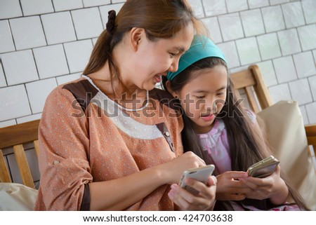 Little Asian mother and daughter playing game on smart phone - stock photo