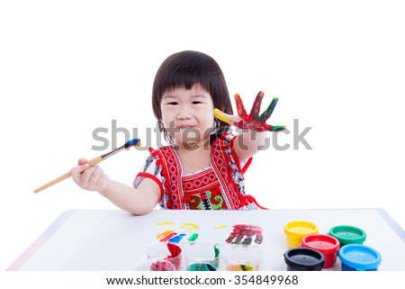 Little asian (thai) child happily. Pretty girl looking at the camera, smiling and paint her hand using multicolored drawing tools, on white background, creativity and education concepts. Studio shot - stock photo