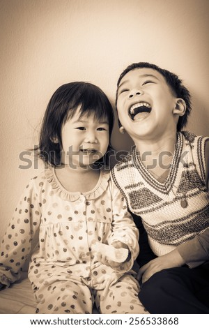 Little asian (thai) children happily, brother laughing and sister smiling, loving and bonding of sibling concept. Cream tone background. Vintage picture style - stock photo