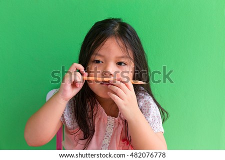 Little Asian Thai girl  holding pencil,Thinking concept ,Girl thinking in class room on green background