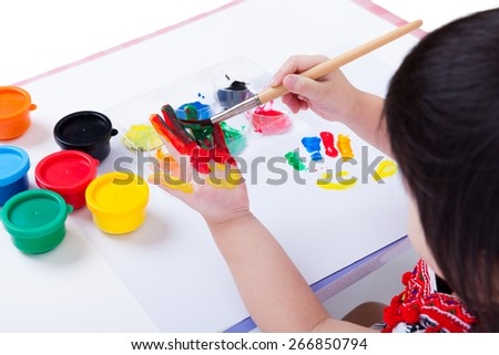 Little asian (thai) girl painting her palm using multicolored drawing tools (watercolor paints, paintbrush), learning, education of art and creativity concept, studio shot - stock photo