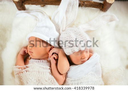 Little babies sleep holding each other arms - stock photo