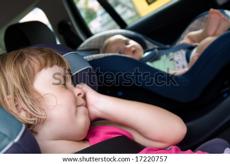 little baby and girl sitting in safety car seat - stock photo