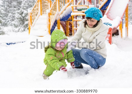 Little baby and mother are playing with first snow in the playground