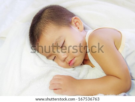 little baby asleep in bed, his head on the pillow close-up.
