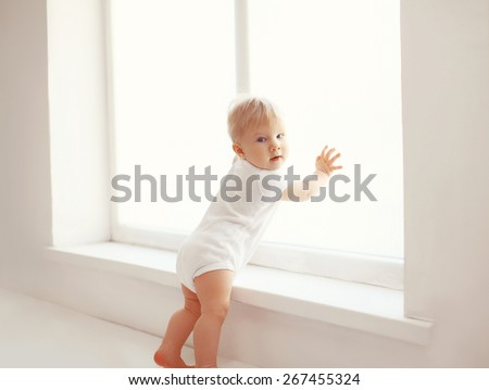 Little baby at home in white room stands near window
