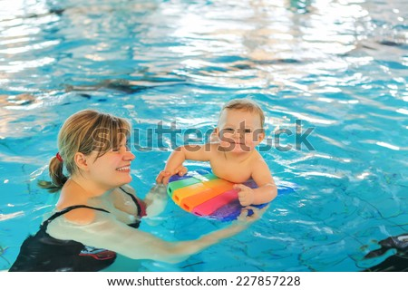 Little baby boy and his mother learning to swim in an indoor swimming pool. Having fun together. Baby swimming concept. - stock photo