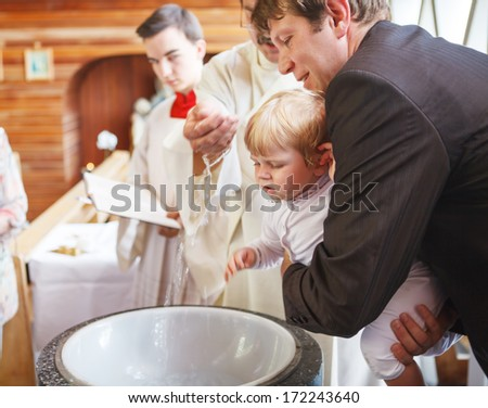 Little baby boy being baptized in catholic church holding by father - stock photo