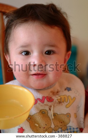 Little baby boy eating cereal and holding up a yellow bow.