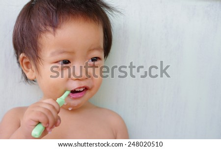little Baby boy enjoy brushing his teeth ,child learning to brush teeth and toothpaste - stock photo