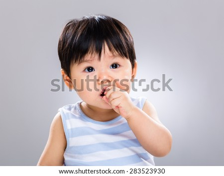 Little baby boy having his cookie - stock photo