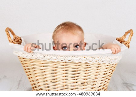 Little baby boy hiding inside the wicker basket