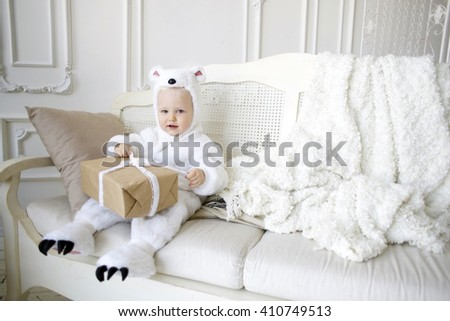 Little baby boy in Christmas costumes white bears sitting in studio