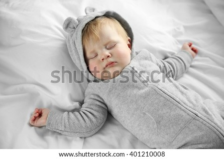 Little baby boy in grey pajamas sleeping on the bed - stock photo