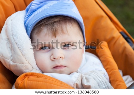 Little baby boy in spring clothes and orange pram outdoor