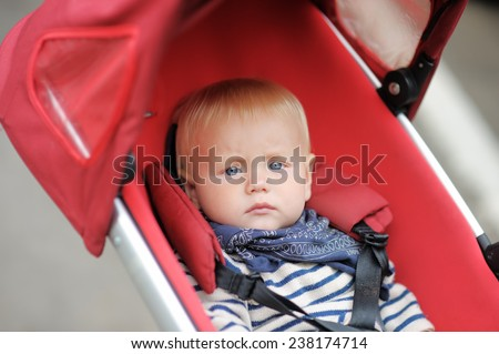 Little baby boy in stroller at the spring day  - stock photo