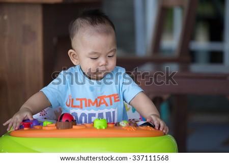 Little baby boy  in the baby walker - stock photo