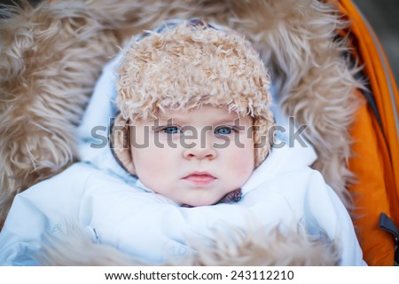 Little baby boy in warm winter clothes and orange pram outdoor. On cold winter day happy toddler sitting and enjoying walking. - stock photo