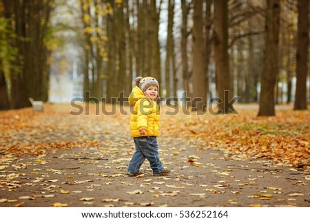 Little baby boy in yellow jacket smiles in autumn