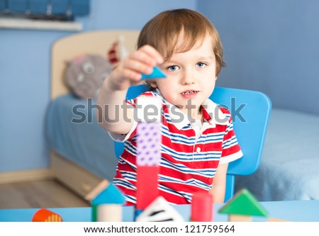 Little baby boy is building with wooden toy blocks - last piece - stock photo