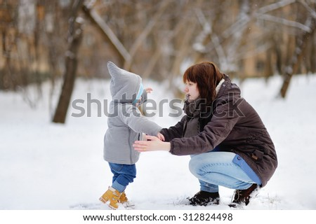 Little baby boy learning to walk. Young woman with her toddler boy at the winter park    - stock photo