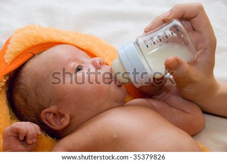 Little baby boy lying at the bed and feeding bottle