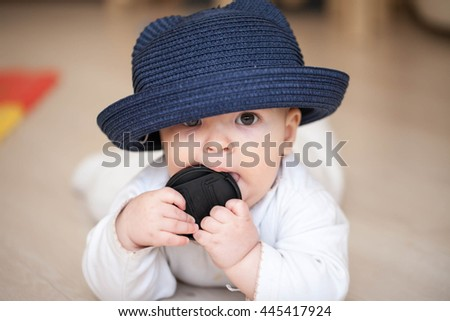 Little baby boy lying on the floor in a large blue hat and eats a black circular cover from the lens, teething and hungry, chewing toy - stock photo