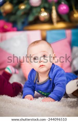 little baby boy lying under the Christmas tree - stock photo