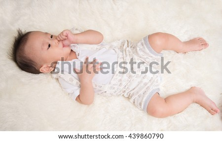 Little baby boy 7 months with sucking his thumb finger in the mouth - stock photo