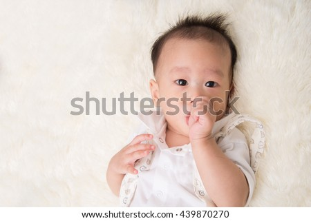 Little baby boy 7 months with thumb finger in the mouth - stock photo