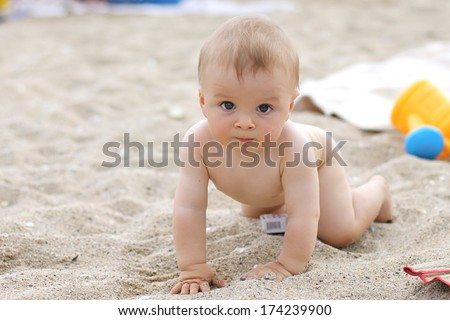 Little baby boy on the beach, playing - stock photo