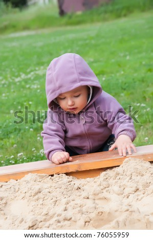 Little baby boy play in the sand box