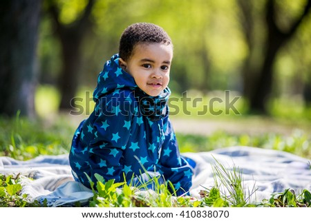 Little baby boy playing on the playground in the spring park. black boy - stock photo
